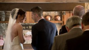 couple laughing during barn ceremony on wedding video in north wales