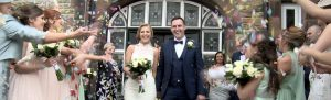 bride and groom laughing and being showered in bright colourful confetti outside a church in Crosby Liverpool caught on video by Love Gets Sweeter wedding films
