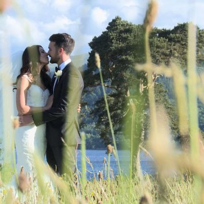 bride and groom having a kiss in the long grass in front of Bassenthwaite lake in Keswick at Armathwaite Hall wedding