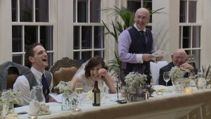 A bride and groom laugh loudly during the father of the bride speech at Mitton Hall near Clitheroe Lancashire due to a rude joke caught on the wedding video