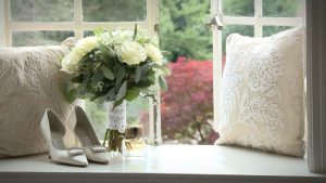 traditional white silk wedding shoes and cream rose bouquet with the brides wedding perfume in the window at Eaves Hall in Clitheroe Lancashire near Preston