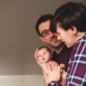 mum and dad with newborn baby on a newborn photo shoot with Kelly Clarke Image Splash