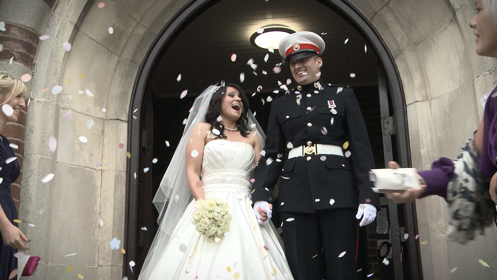 a groom in military dress and bride in white laugh as they stand in their wirral church doorway being showered in confetti for the wedding video