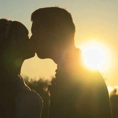 lens flare during sunset as a bride and groom kiss during their Malkin Bank golf wedding in cheshire with their wedding videographer Love Gets Sweeter