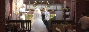 bride and groom kneel for a blessing during their wedding ceremony in lancashire with love gets sweeter as their videographer