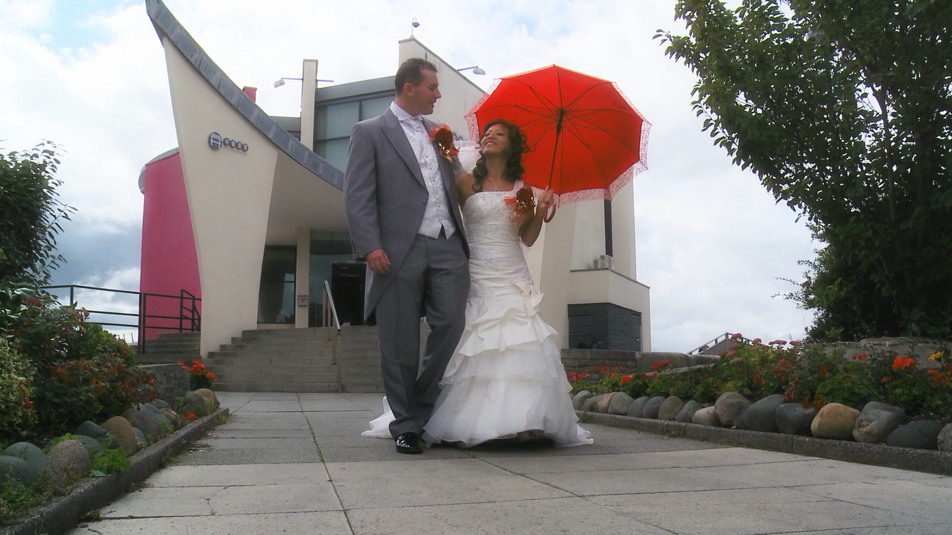 A bride and groom walk towards the videographer as the bride holds a traditional red chinese umbrella before their wedding reception at Chung Ku by the liverpool waterfront