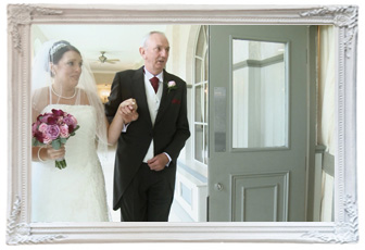 a nervous bride with her wedding veil over her face holds her dads hand before she starts to walk down the aisle at Mottram Hall