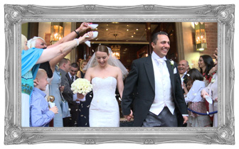 The bride wearing a simple sweetheart neck Stewart Parvin wedding dress and holding a cream rose bouquet walks out of the Chester Grosvenor in Cheshire holding her husbands had as their guests throw confetti over them and laugh for the wedding video