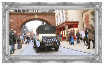 A traditional cream and black wedding car with a Just Married sign on the back drives away from the Chester Grosvenor and under the famous roman walls as their wedding videographer films