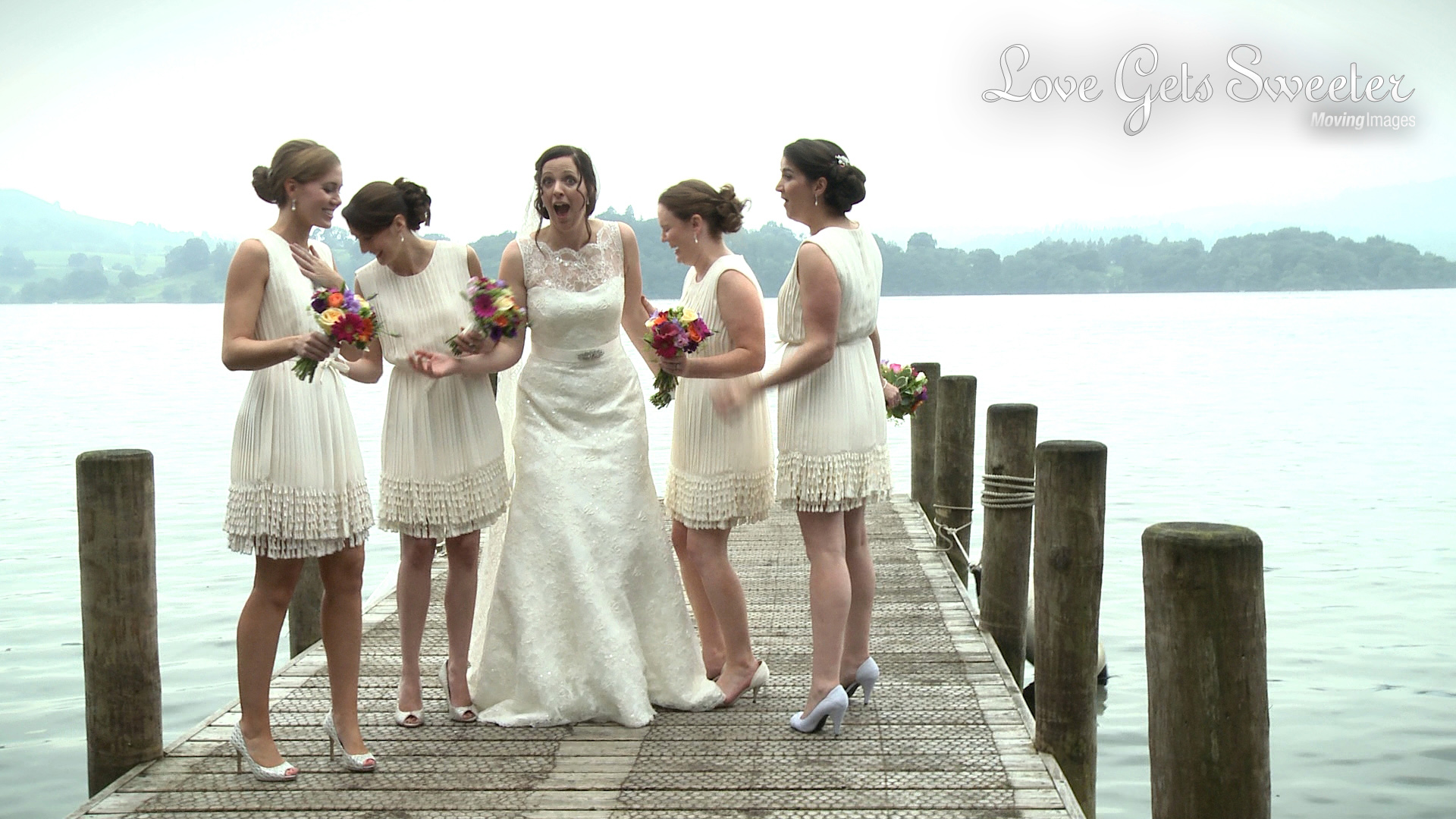 wedding video still of A bride looking shocked with her bridemaids nearly fall in standing on a jetty outside The Langdale chase Hotel on Lake Windermere