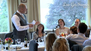 the bride smiles up at her dad during his Father of the Bride speech at their wedding at Langdale Chase Hotel over looking Lake Windermere