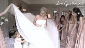 A beautiful bride stands in the bridal suite at Thornton Manor with her bridesmaids wearing pink two bird bridesmaid dresses. They're helping her get ready as a cute toddler flower girl goes under her dress