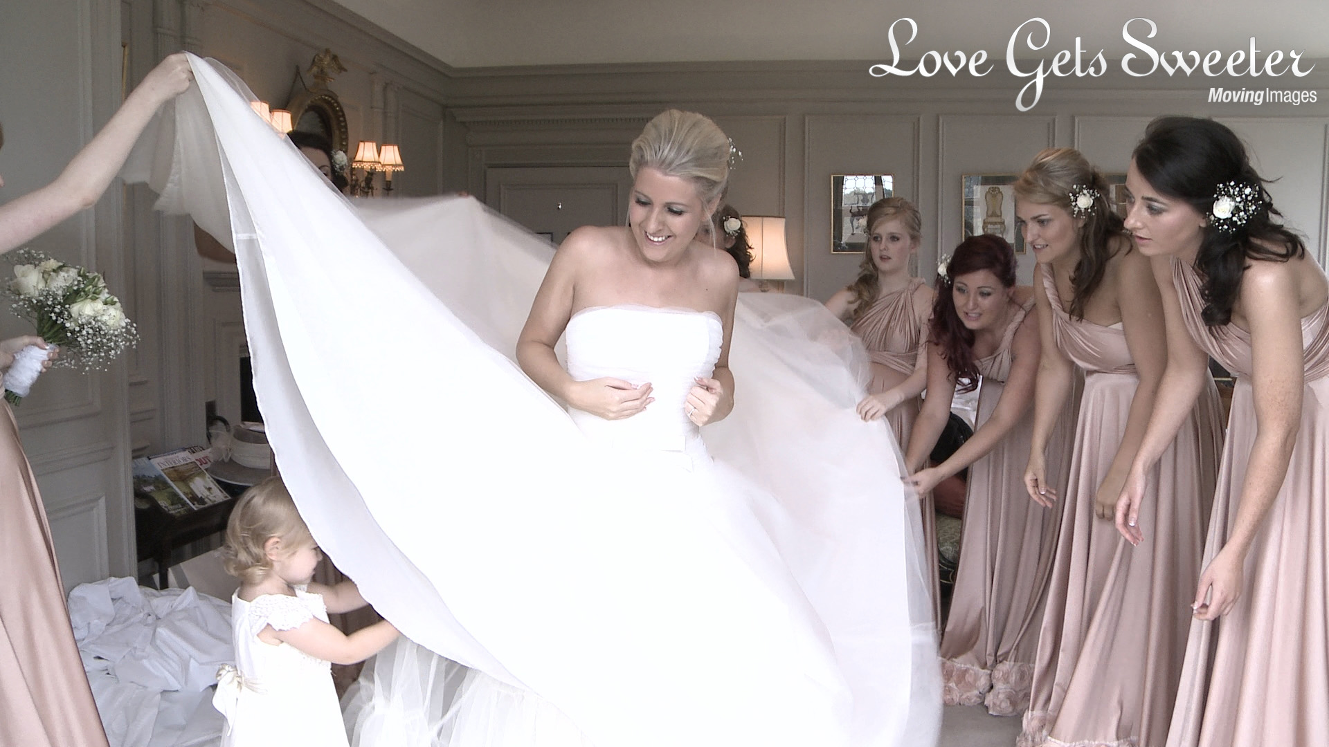 bride in Stewart Parvin wedding gown with her bridesmaids in two bird pink bridesmaid dresses watching the cute flower girl help under the brides dress at thornton manor in the wirral