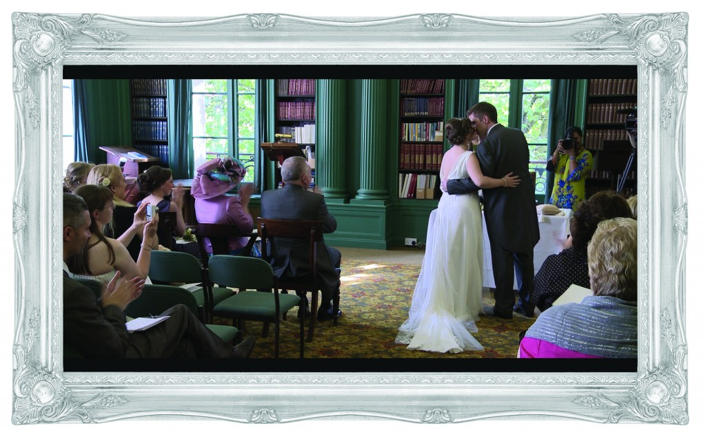 The bride and groom hold each other close and kiss during their wedding ceremony at the Liverpool Athenaeum in front of their wedding videographer