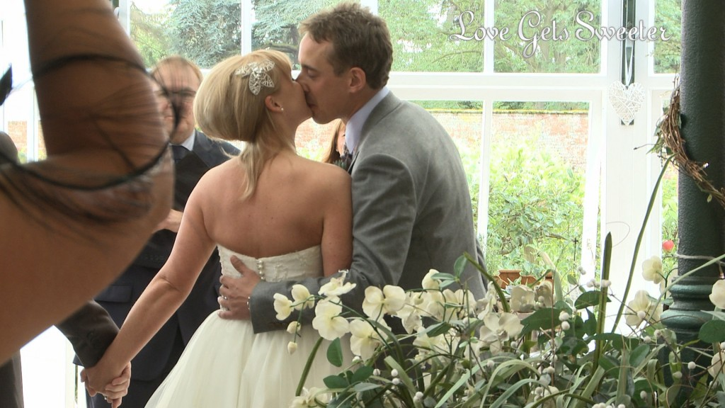 Liam the Groom gives his wife to be a huge kiss as she meets him at the bottom of the aisle in the glasshouse at Combermere abbey before their wedding ceremony starts