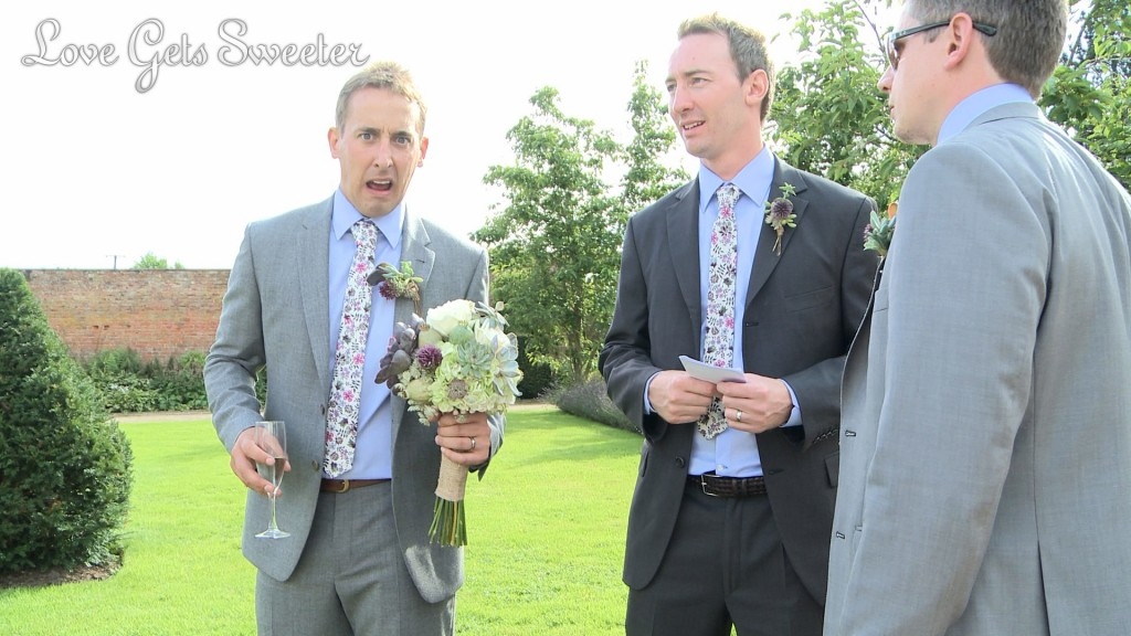 Liam the groom pulls a face at the wedding videographer as he's left to hold the brides bouquet during their wedding photos at Combermere Abbey