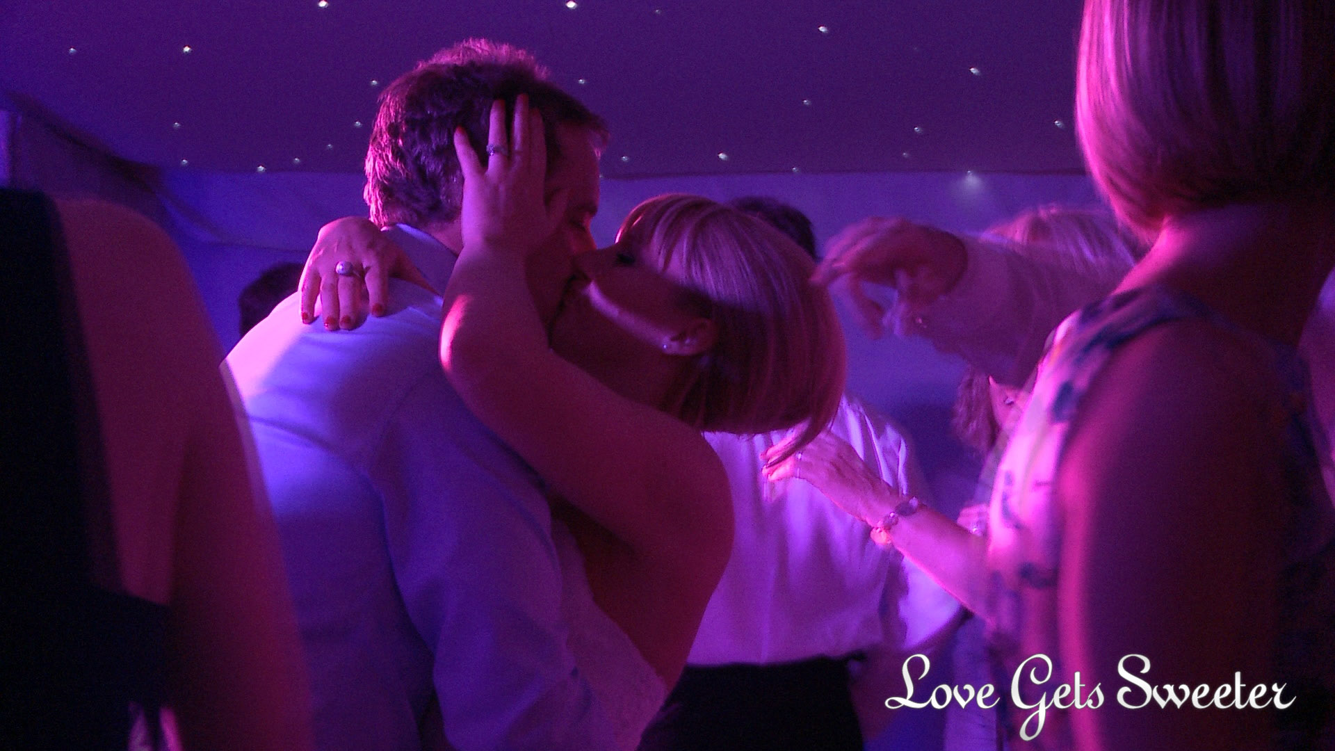 a bride and groom have a passionate kiss on the dancefloor as their guests dance around them during their wedding reception at Combermere Abbey in Cheshire