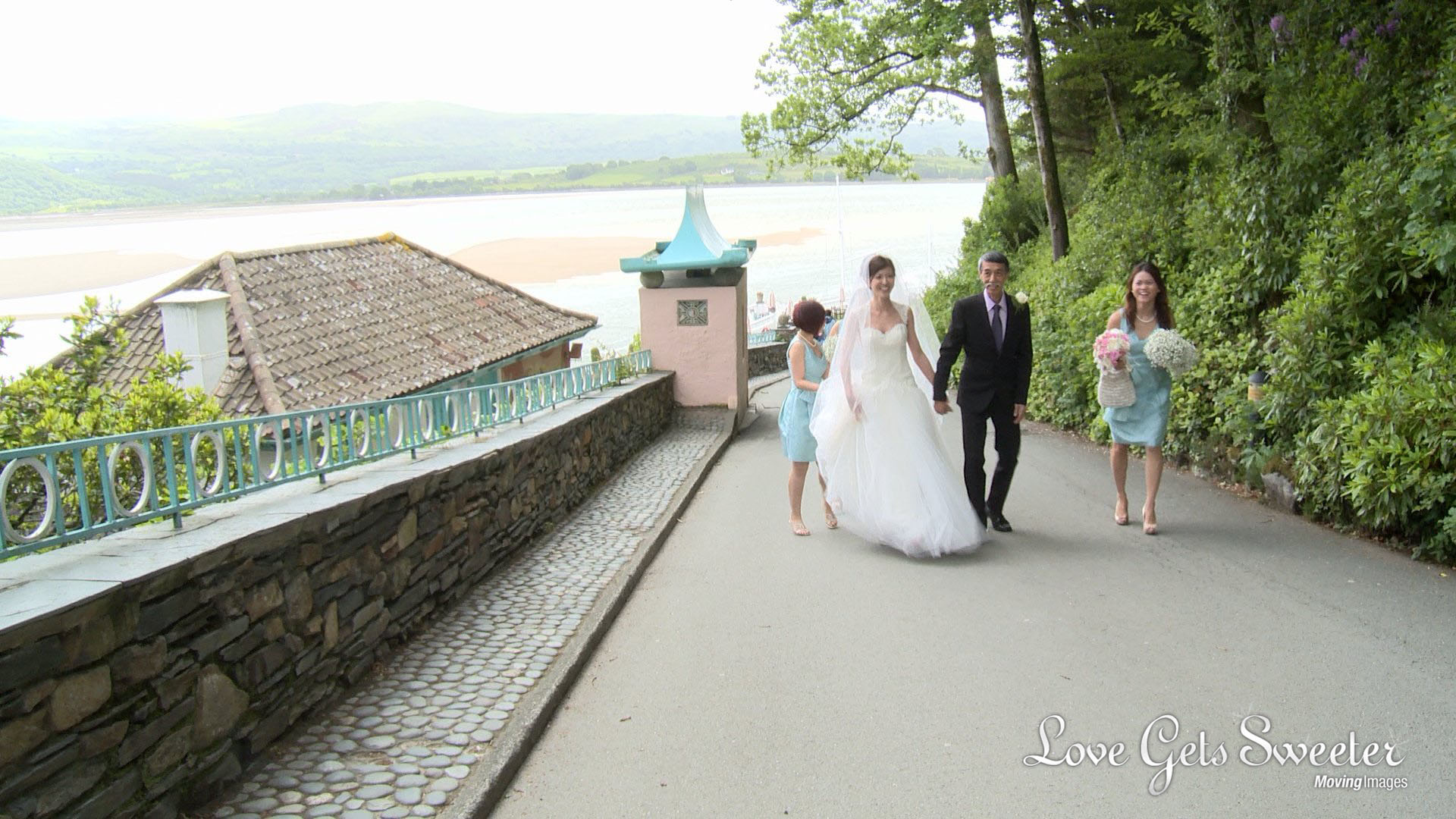 a bride and her two bridesmaids wearing mint green walk up the hill at portmeirion towards the ceremony room being filmed by the wedding videographer Love Gets Sweeter