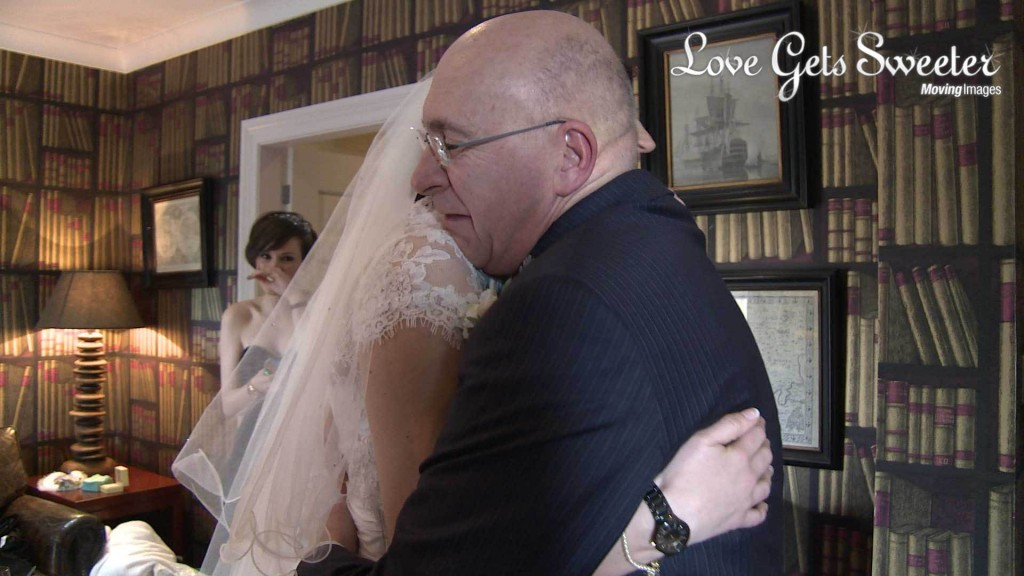 A video still of A father of the bride gives his daughter an emotional bear hug with tears in his eyes as he sees her for the first time before she gets married at Mitton Hall