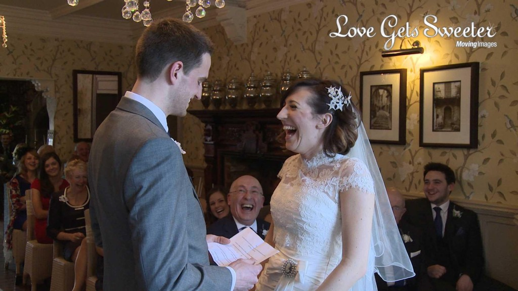 the bride wearing Stewart Parvin laughs along with the guests during the grooms personal vows about loving her more than Liverpool football club at their wedding ceremony at Mitton Hall
