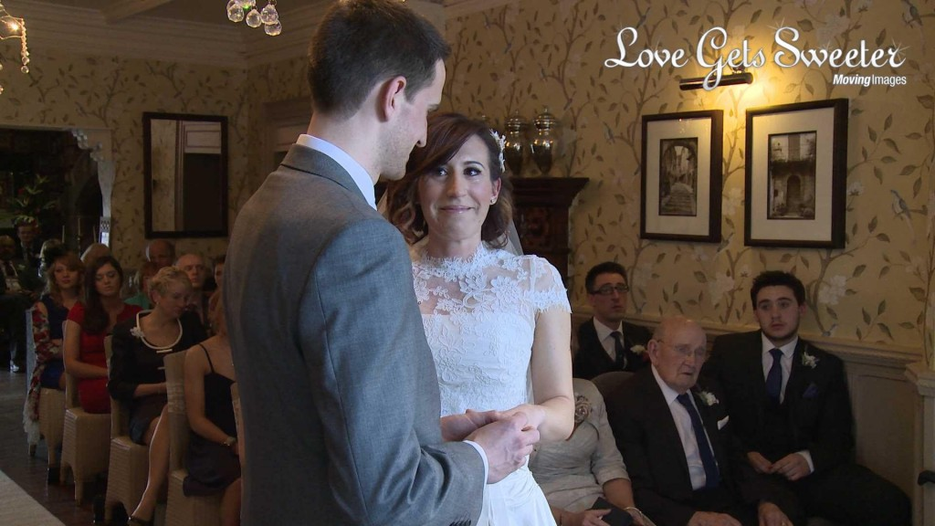 Keri the bride smiles with tears in her eyes as she exchanges wedding rings on her wedding day at Mitton Hall