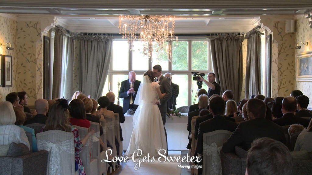 The bride and groom pull each other close and have a kiss as they're announced husband and wife in front of their guests, wedding photographer and videographer too, at Mitton Hall in Clitheroe Lancashire