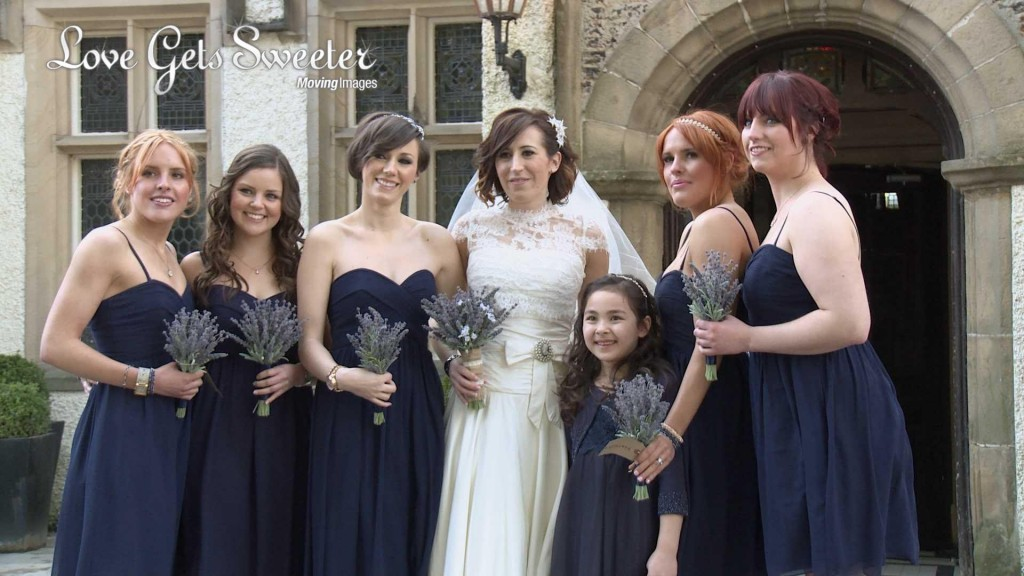 a bride wearing stewart parvin lace and silk wedding dress holding lavender faux flowers poses with her bridesmaids wearing floor length navy blue coast dresses as Mick Cookson takes photos and love gets sweeter video outside Mitton Hall