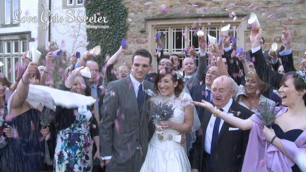 the bride and groom are showered in natural purple and cream wedding confetti for the photo and video outside Mitton Hall near Clitheroe