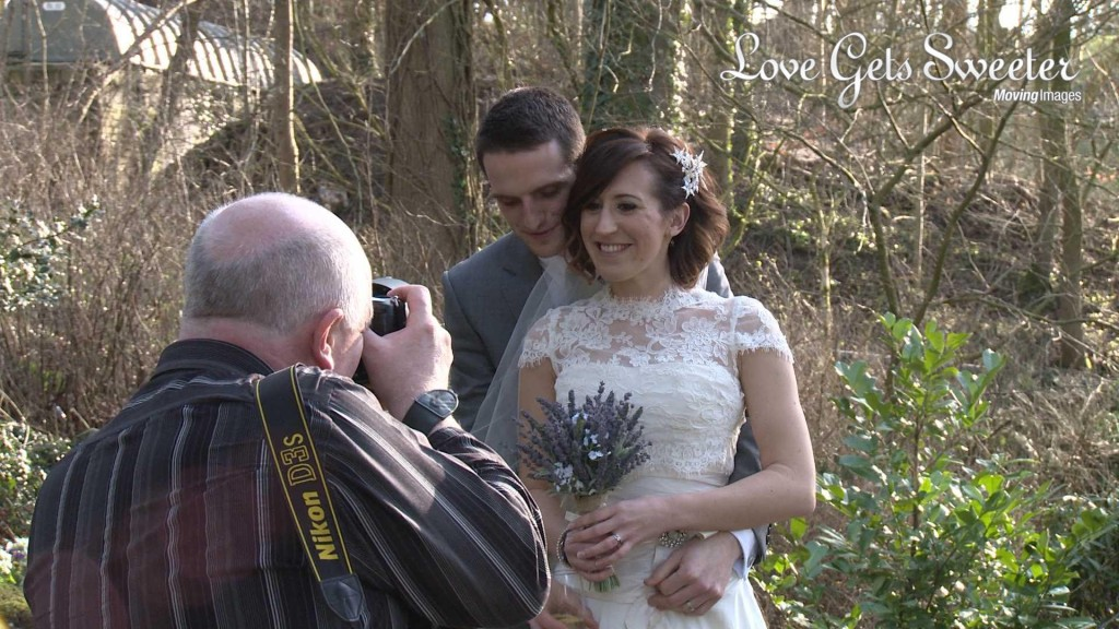a video still of Mick Cookson the wedding photographer posing and taking photos of a bride and groom in the gardens at mitton hall