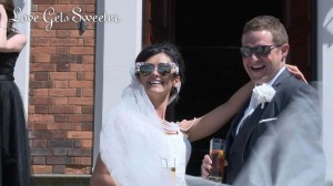 a bride and groom laugh as they pose on the steps of Knowsley hall for their wedding photographer and videographer wearing fun sunglasses for their hot summer wedding in Merseyside