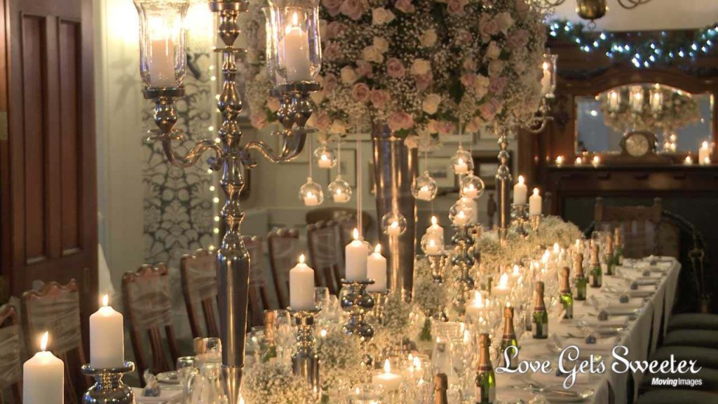 a stunning and romantic winter wedding breakfast table at Broadoaks country house hotel. The table is full of candles and towering white and blush rose centrepieces by Red Floral
