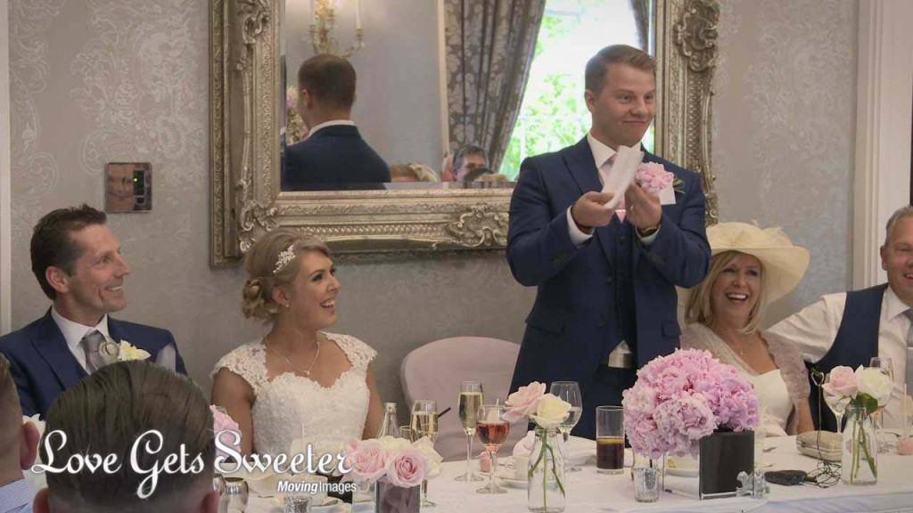 A wedding video still from the grooms speech at Oulton Hall in Leeds. He makes the top table laugh by showing off his queue cards