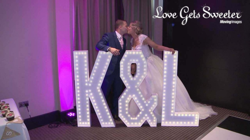 A still from Katy and Lukes wedding video of them kissing behind large light up letters of their initials K & L at their wedding reception at Oulton Hall