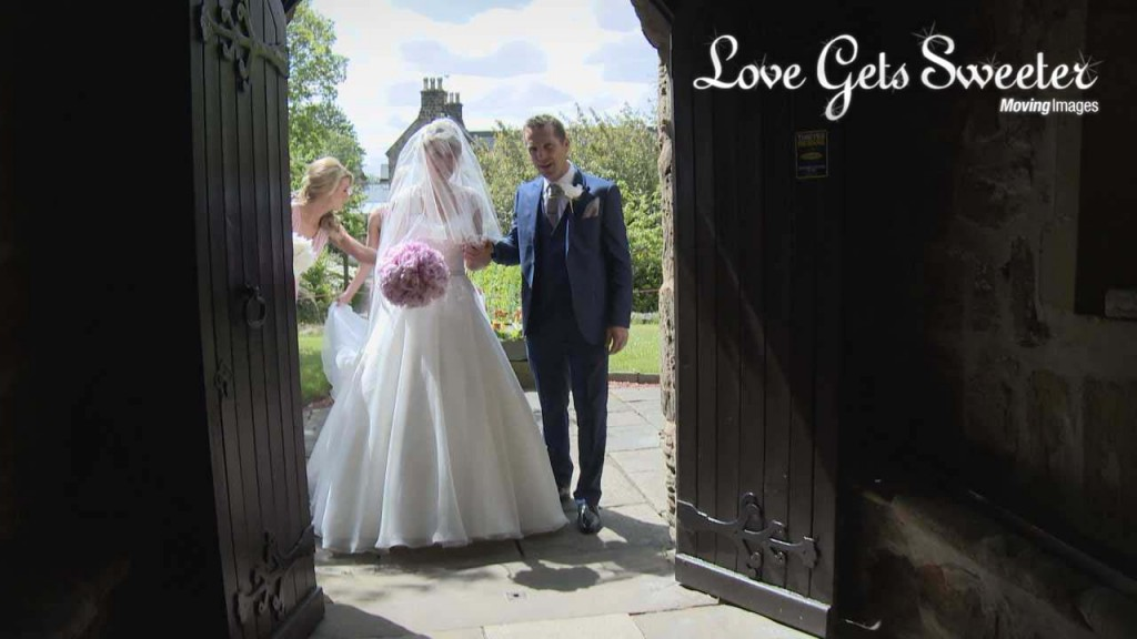 The bride and her dad wait outside the church doors before she walks down the aisle. A bridesmaid is arranging her veil and train for her. A still from the wedding video
