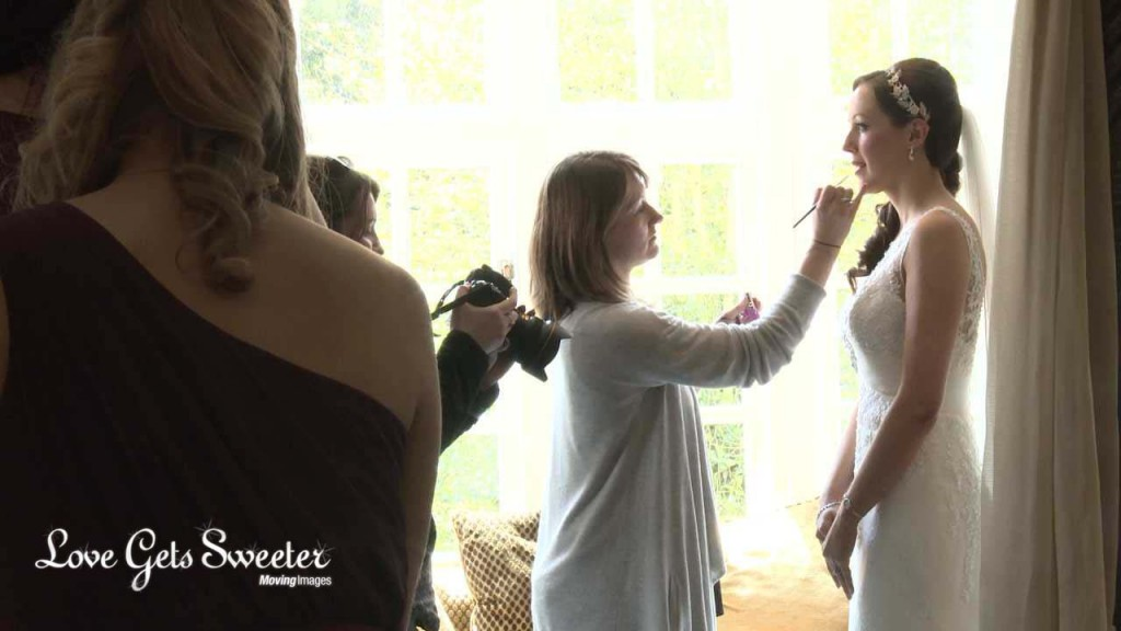 the bride stands by a bright window in a suite at the Mere Court Hotel near Knutsford as her wedding makeup artist applies her lipstick. This is a video still from Love Gets Sweeter