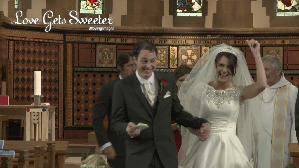 the bride punches the air for the wedding video as they both walk back down the aisle after their wedding ceremony at Dalton Church in Lancashire before heading to their reception at West Tower