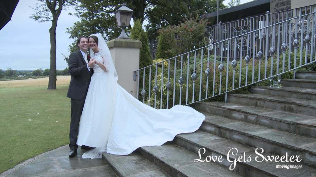 a wedding video still of a very happy and slightly tipsy bride and groom standing on the steps outside West Tower for some photographs with Ian MacMichael in Lancashire