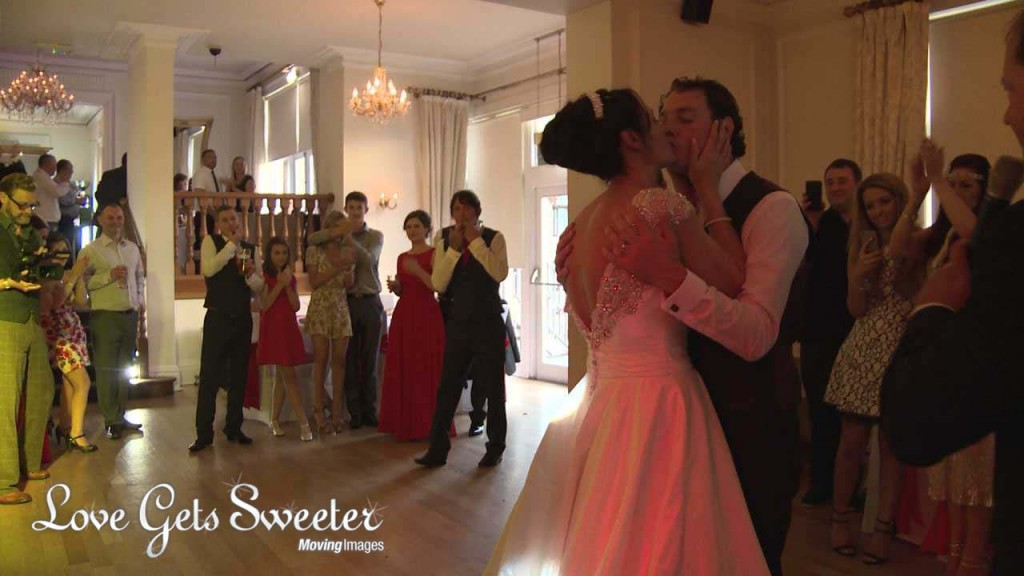 a wide shot from the wedding videographer of the bride and groom having a kiss during their first dance at their west tower wedding reception in Lancashire