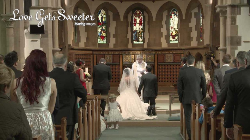a video still from the back of Dalton Church as the bride and groom kneel during their wedding ceremony for the blessing. A cute flower girl wanders around the aisle