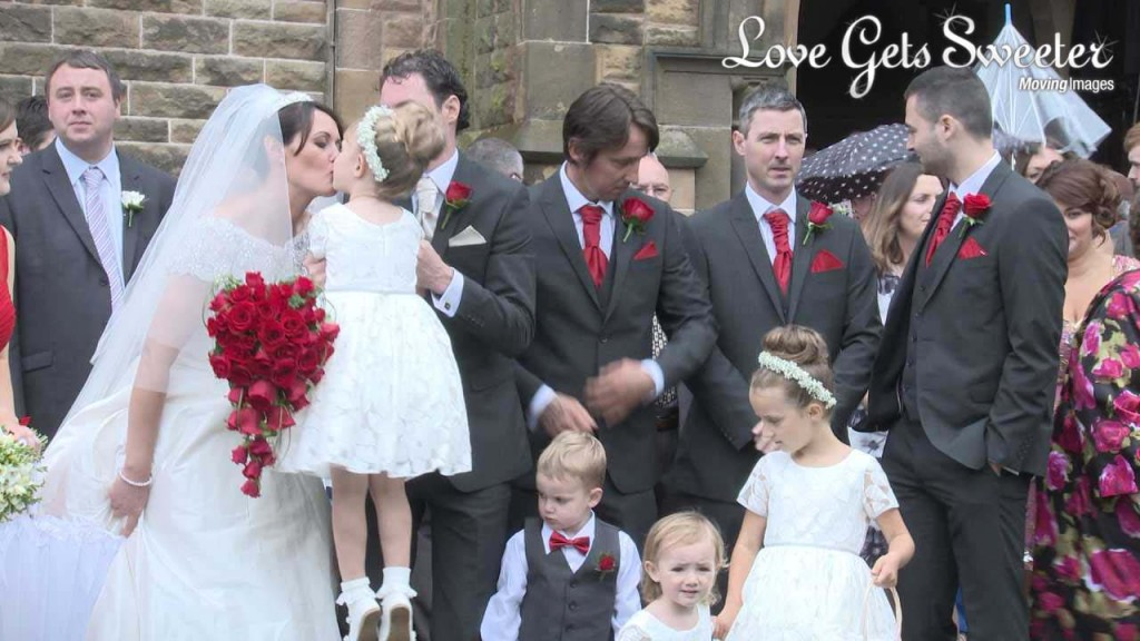 The groom lifts up one of their daughters during the wedding photographs so the bride can have a kiss. She holds a traditional heart shaped red rose bridal bouquet and the wedding party wear red ties for their white and red themed wedding