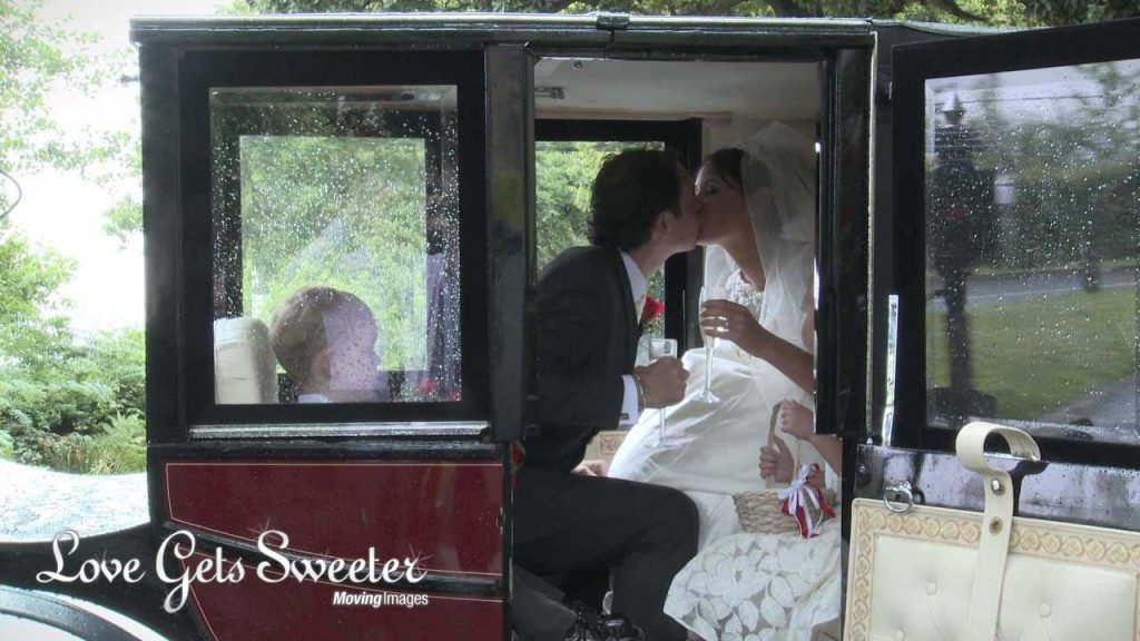 a wedding video still of a bride and groom newlyweds sitting inside their wedding horse and carriage and having a kiss holding their champagne after their wedding ceremony at Dalton Church