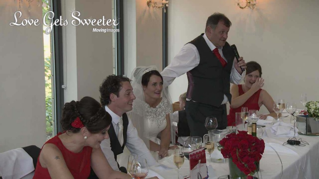 A wedding video still during the wedding speeches of a bride looking mortified during the father of the bride speech at their West Tower wedding in Aughton Lancashire. Bright red roses add to the red and white colour scheme.