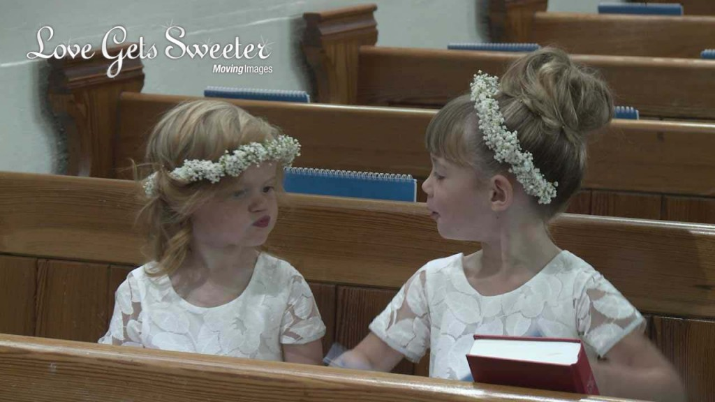 2 very cute flower girls wearing white gypsy grass flower crowns sit in a pew at Dalton Church. One is pouting at the other