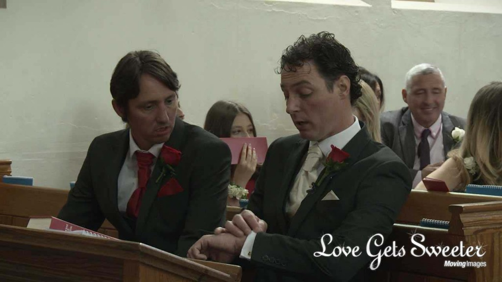 The groom sits next to his best man in a pew at Dalton St Micheal and All Angels church looking at his watch before the bride arrives for their wedding ceremony