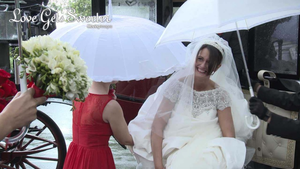 our bride Helen steps out of her red and black horse drawn carriage in to the rain as her bridesmaids wearing red try to help hold her dress up as well as the white umbrellas. She has a huge grin on her face as she laughs at the fuss. Filmed for their wedding video outside Dalton Church St Michael and All Angels Church in Lancashire