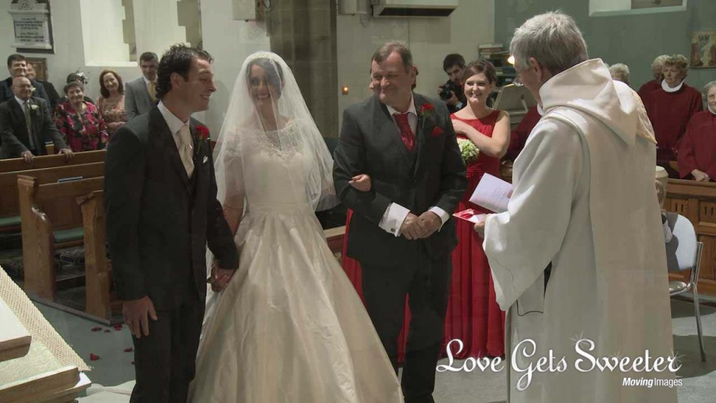 a very proud dad looks on as his daughter meets her groom at Dalton Church with her veil still over her face. Her bridesmaids stand to the side wearing floor length red bridesmaid dresses