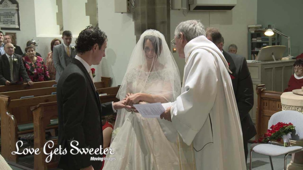 A bride and groom exchange wedding rings in front of the wedding videographer at Dalton St Michaels and All Angels Church in Lancashire