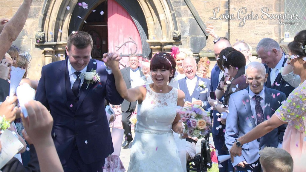 a wedding video still of the bride and groom holding hands as they get showered in confetti by their wedding guests outside their church in New Brighton