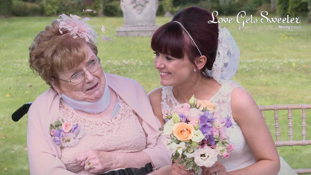 Siobhan the bride leans in to hug and smile at her Mum who is in a wheelchair as they have wedding photos done at Thornton Manor