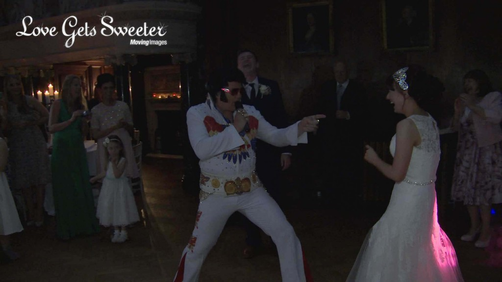 The bride and groom laugh as the surprise Elvis impersonator performs for their wedding first dance at Thornton Manor in the wirral. This is a still taken from their wedding highlights video